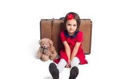 小女孩微笑带着手提箱的和玩具负担 免版税库存照片