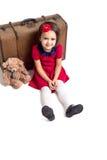 小女孩微笑带着手提箱的和玩具负担 免版税图库摄影