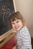 小女孩微笑感到骄傲为花她的图画在blackboar的 免版税库存图片
