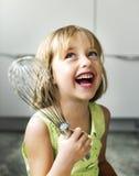 小女孩微笑烘烤曲奇饼概念 免版税库存照片