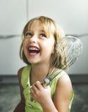 小女孩微笑烘烤曲奇饼概念 免版税图库摄影