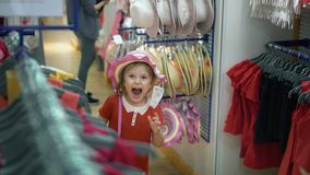 小女孩微笑,尝试在帽子和提包在商店 影视素材