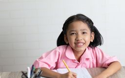 小女孩愉快地做着家庭作业和微笑 免版税图库摄影