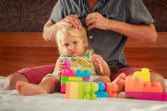 小女孩戏剧玩具建设者父亲掠过她的头发 图库摄影