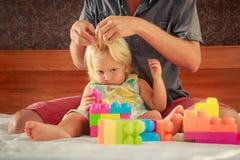小女孩戏剧玩具建设者父亲掠过她的头发 免版税库存图片
