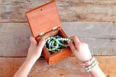 小女孩打开一箱镯子 背景老木 免版税库存照片