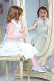 小女孩打扮敬佩她的在镜子的反射 免版税库存照片