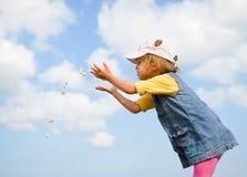 小女孩投掷石头 免版税库存照片