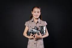 小女孩拍与葡萄酒照相机的照片在黑背景 免版税库存照片