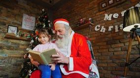 小女孩拥抱圣诞老人并且愉快地微笑 r 免版税库存照片