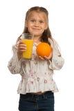 小女孩拿着一块玻璃用橙汁单手和 库存图片