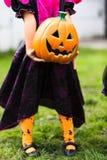小女孩拿着橙色起重器o灯笼万圣夜装饰 库存图片