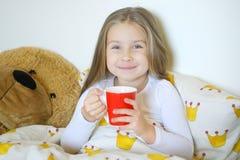 小女孩捉住了流感和饮用的热的茶用柠檬在床上 图库摄影