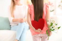 小女孩掩藏的毛毡心脏和花为母亲` s天 免版税库存图片