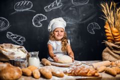 小女孩揉的面团在桌上 免版税库存照片