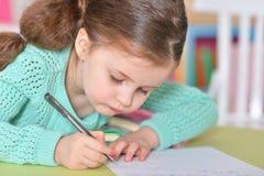 小女孩文字,当坐在桌上时 免版税库存照片