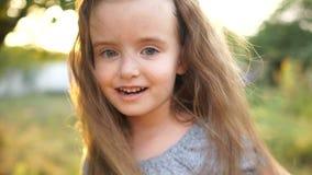 小女孩无所事事,摇她的头,并且头发,从她的面孔取消她的头发 孩子是愉快的 特写镜头 股票录像