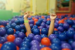小女孩是在球坑的塑料球下 免版税库存照片