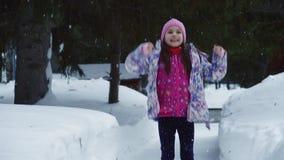 小女孩是跳和享用第一雪 孩子通过夹克和帽子的冬天森林走 慢 股票视频
