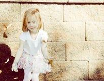 小女孩有吹她的头发的风的投掷叶子 免版税库存照片