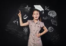 小女孩有想法在黑板附近 孩子显示手指  免版税库存照片