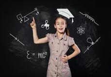 小女孩有想法在黑板附近 孩子显示手指  免版税库存图片