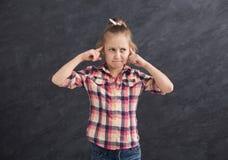 小女孩有手指的覆盖物耳朵 免版税库存照片