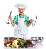 小女孩有新鲜蔬菜的厨师厨师 库存图片