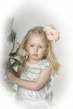 小女孩有玫瑰的儿童金发碧眼的女人在她的头发 免版税库存照片