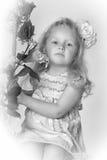 小女孩有玫瑰的儿童金发碧眼的女人在她的头发 库存图片
