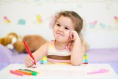 小女孩油漆在托儿所在家 图库摄影