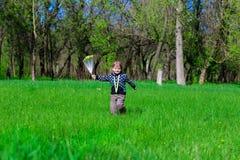 小女孩沿与花的绿草跑 免版税图库摄影