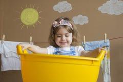 小女孩洗涤衣裳,并且垂悬在绳索烘干 概念性家事 婴孩帮助妈妈 免版税库存照片