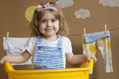 小女孩洗涤衣裳,并且垂悬在绳索烘干 概念性家事 婴孩帮助妈妈 库存照片