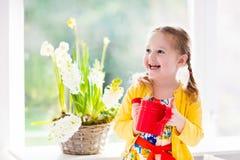 小女孩浇灌的春天花 免版税图库摄影