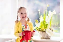 小女孩浇灌的春天花 库存照片