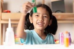 小女孩测试在玻璃和看的颜色 库存图片