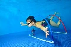 小女孩游泳和戏剧体育水下在蓝色背景的水池和浮游物通过箍在底部 免版税库存照片
