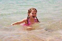 小女孩游泳在海。暑假。 免版税库存图片