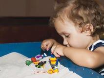 小女孩演奏在沙子的玩具 免版税库存照片