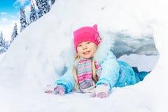 小女孩爬行通过雪隧道在公园 库存照片