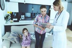 小女孩生了病 医生来看她 女孩吹她的在餐巾的鼻子 库存照片