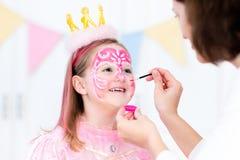 小女孩生日聚会的面孔绘画 库存图片