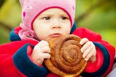 小女孩用一个小圆面包在手上 免版税库存图片
