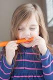小女孩用一棵长的红萝卜 免版税库存图片
