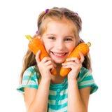 小女孩用两棵红萝卜 免版税库存照片