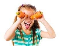 小女孩用两棵红萝卜 库存照片