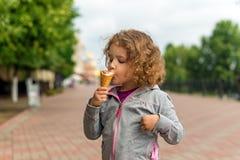 小女孩用冰淇凌在公园 免版税库存图片