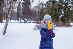 小女孩用在冬天公园的甜玉米 免版税库存图片