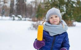 小女孩用在冬天公园的甜玉米 免版税库存照片